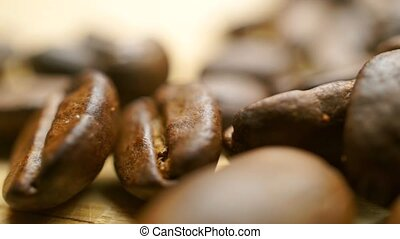 Pile of roasted coffee beans on light wooden table. Shallow focus macro pan shot
