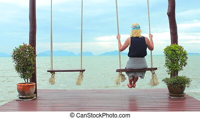 A woman on a swing by the sea