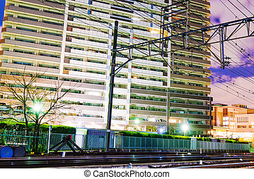 Apartment buildings at night by a railway track in Japan