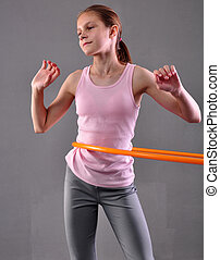 Teenage sportive girl is doing exercises with hula hoop to...