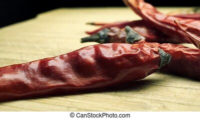 Macro pan shot of pile of dried red hot peppers. Bleached...