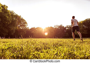 A handsome young man running towards the sunset - A handsome...