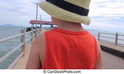 Little boy is on the pier
