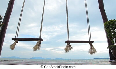 Rope swings by the sea - Swings on the background of blue...