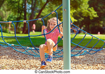 Little girl playing at playground in summe - Happy little...
