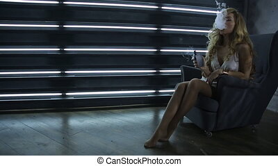 Woman sits in armchair, smokes electronic cigarette and...