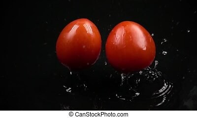 Super slow motion of two red ripe tomatoes hitting dark wet...