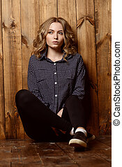 loneliness - Casual teen girl sitting by a wooden wall Youth...