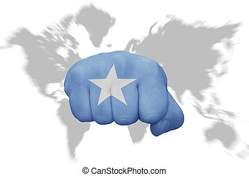 fist with the national flag of somalia on a world map...