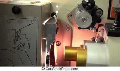 Pulling 35 mm film in professional film cinema projector, 4K...