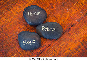 Black inspirational pebble stones with the words Dream, Believe and Hope on wooden background