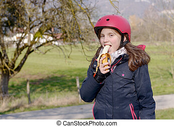 preteen with roller skate helmet, eat banana