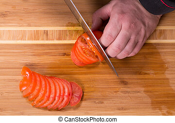 The chef cuts the tomatoes