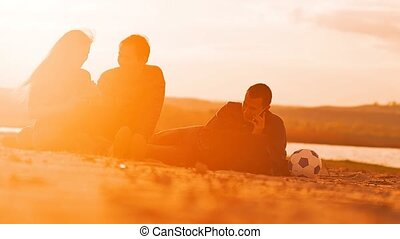 Three friends sitting on the sand communicate Slow motion...