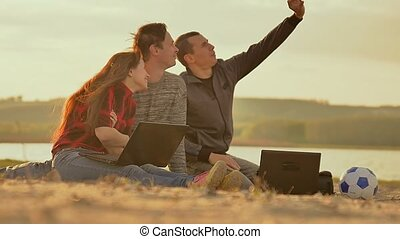 selfie in the sand three friends with laptops Slow motion...