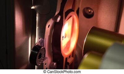 Dolly video of optical parts in film cinema projector in...