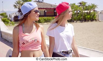 Beautiful and confident female friends near beach wearing...