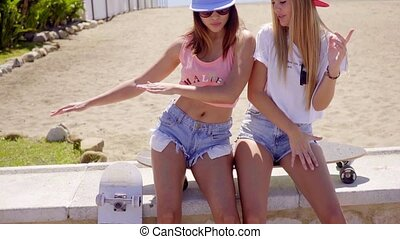Two young friends in shorts sitting near beach - Two cute...