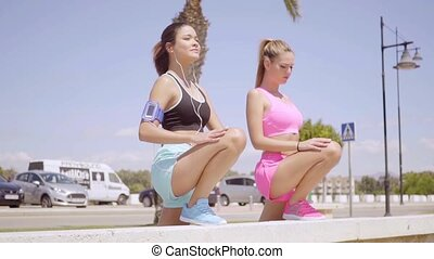 Pretty blond and brunette female friends stretch on stone...