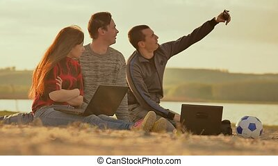 three friends with laptops doing selfie Slow motion video -...