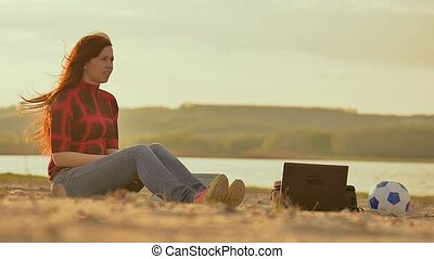 with a laptop girl sitting on the sand Slow motion video -...
