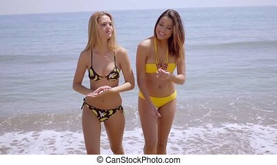 Two lovely young women wearing bikinis walking out of the...