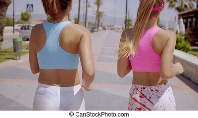 Two healthy young women jogging together