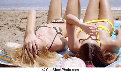 Two young women tanning in their bikinis in the hot summer...
