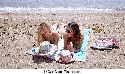 Two sunbathing friends on a beach by the ocean