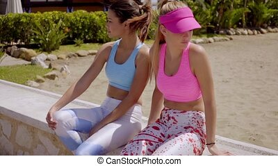 Two trendy young woman sitting waiting or resting on a low...