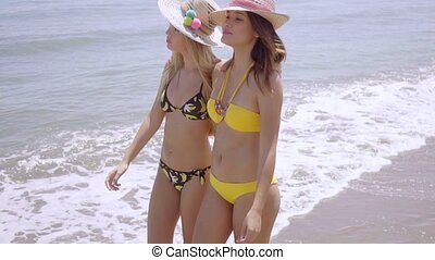Two trendy young woman strolling along a beach in their...