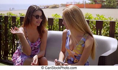 Two young women relaxing at an outdoor cafe - Two young...