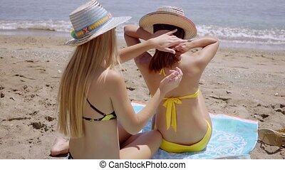 Young woman applying sunscreen to a friend - Young woman...
