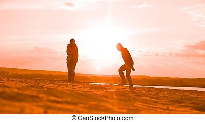 girl in jacket stands a man kicking a ball in the sand Slow...