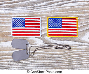 Small USA flag patches and military ID tags on rustic white...