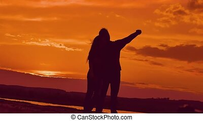 silhouettes of a woman with a man at sunset shoot selfie -...