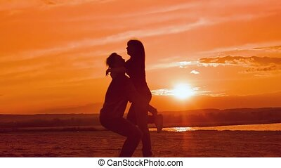 at sunset girl runs and hugs guy slow motion video - at...