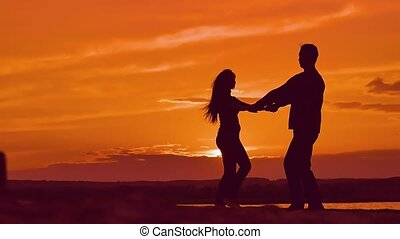 at sunset girl and boy holding hands circling slow motion video