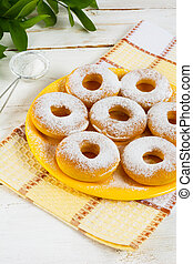 Caster sugar powdered donuts on yellow plate. Sweet dessert....