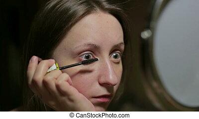 Makeup at home girl pass mascara in eyes
