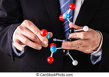 mounting a tnt molecular structure - a businessman wearing a...