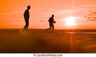 dark silhouettes of two men playing volleyball slow motion...