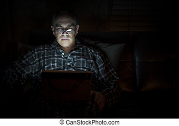 Man reading tablet at night - Middle aged man wearing...