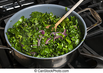 Cooking kale - Fresh kale sauteed with onions in a cooking...
