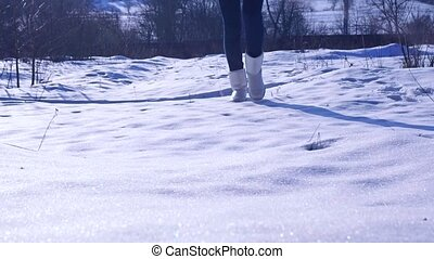 Girl in silver winter boots walking on sunny snow. Zoom out...