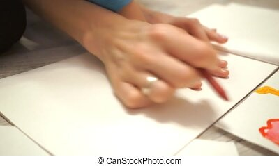 Young woman and her child drawing hand outline with crayon...