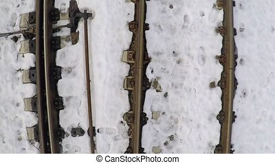 Very low altitude smooth aerial shot of railroad tracks and switches under snow