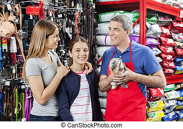 Family Standing With Salesman Holding Rabbit At Store -...