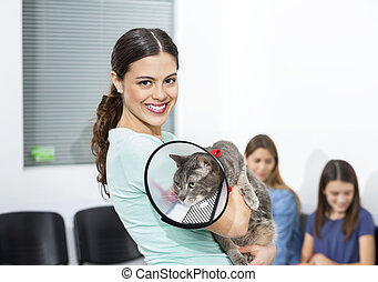 Woman Holding Cat With Cone In Clinic - Portrait of smiling...