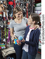 Mother And Daughter Buying Toys For Pet - Happy mother and...